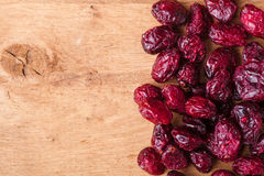 Diet healthy food. Border of dried cranberries on wooden background Royalty Free Stock Images