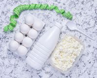 Diet, healthy food. Bottle of yogurt, cottage cheese, plastic egg tray on a white concrete background. Ruler for waist measurement. The concept of losing stock images