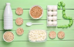 Diet, healthy food. Bottle of yogurt, crispy round bread, buckwheat noodles, oatmeal, cottage cheese, egg tray on a blue wooden b. Ackground. Ruler for waist royalty free stock photo