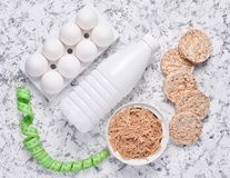 Diet, healthy food. Crispy round dietary bread, a bottle of yogurt, buckwheat noodles, plastic egg tray on a white concrete. Background. Ruler for waist royalty free stock photos