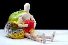 Diet with healthy fruit. Wooden mannequin with healthy food while on diet stock photography