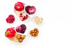 Diet for healthy heart. Food with antioxidants. Vegetables, fruits, nuts in heart shaped bowl on white background top. View royalty free stock photos