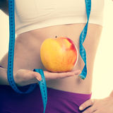 Diet healthy nutrition. Fit girl with measure tape, fruit apple. Royalty Free Stock Image