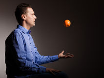 Diet and healthy nutrition. Man throwing orange Royalty Free Stock Photos