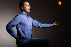Diet and healthy nutrition. Man throwing orange Stock Photography