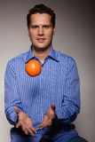 Diet and healthy nutrition. Man throwing orange Royalty Free Stock Photo