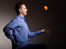 Diet and healthy nutrition. Man throwing orange. Diet and nutrition. Young smiling man throwing orange tropical fruit on gray. Happy guy recommending healthy stock images