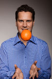 Diet and healthy nutrition. Man throwing orange Royalty Free Stock Images