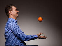 Diet and healthy nutrition. Man throwing orange Royalty Free Stock Photography