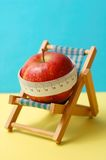 Diet during holidays. Healthy holidays, conceptual photo. An apple on a deckchair and measuring tape Stock Photos