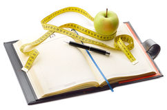 Diet journal. Notebook and pen with apple and measuring tape for writing the diet notes Royalty Free Stock Images