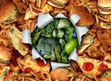 Diet Lifestyle Change. Concept and breaking out and escape from unhealthy habits of eating fatty junk food towards green vegetables and fruit as a ripped and Royalty Free Stock Photo