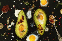 Diet lunch - baked avocado and quail eggs Stock Photos