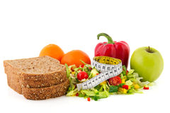 Diet meal with measuring tape. Diet meal with brown bread mixed salad and fruit and measuring tape Royalty Free Stock Photos