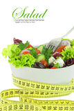 Diet Salad. Vegetables in a bowl with measuring tape Royalty Free Stock Image