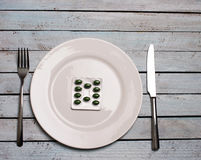 Diet or  medicine abuse concept - green pills in plate with knif. E and fork on wooden grunge table Stock Photo