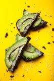 Diet-mellanmål med svart bröd med avokado-, gräddost- och sesamfrö på en gul bakgrund royaltyfri foto