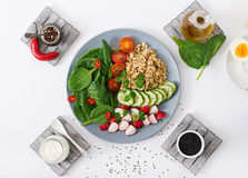 Diet menu. Healthy lifestyle. Vegan salad of fresh vegetables - tomatoes, cucumber, radish, spinach and oatmeal Royalty Free Stock Images