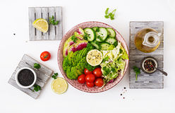 Diet menu. Healthy lifestyle. Vegan salad of fresh vegetables - tomatoes, cucumber, watermelon radish and avocado Royalty Free Stock Image