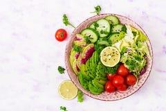 Diet menu. Healthy lifestyle. Vegan salad of fresh vegetables - tomatoes, cucumber, watermelon radish and avocado Stock Image