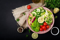 Diet menu. Healthy lifestyle. Vegan salad of fresh vegetables - tomatoes, cucumber, watermelon radish and avocado. On plate. Flat lay. Top view stock photography