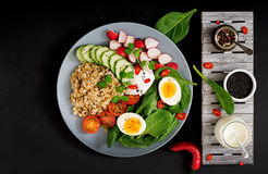 Diet menu. Healthy salad of fresh vegetables - tomatoes, cucumber, radish, egg, spinach and oatmeal Stock Photography