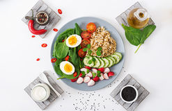 Diet menu. Healthy salad of fresh vegetables - tomatoes, cucumber, radish, egg, spinach and oatmeal Stock Photo