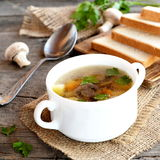 Diet mushroom soup with vegetables, sliced white bread on a kitchen cutting board, spoon, parsley, fresh agaricus on a wood table Royalty Free Stock Photography