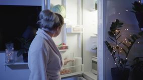 Diet and night hunger, girl on kitchen opens the refrigerator to eat hamburger but takes glass of water and drinks it