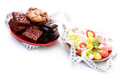 Diet or not. Plates full of salad and sweet food - diet and breakfast Royalty Free Stock Photo