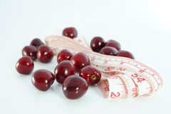 Diet and nutrition.  Cherries with measuring tape on white background Royalty Free Stock Images