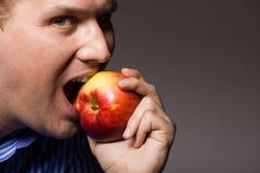 Diet nutrition. Happy man biting apple fruit. Diet and nutrition. Happy young man eating biting apple seasonal fruit on dark gray. Guy recommending healthy stock photos