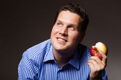 Diet nutrition. Happy man eating apple fruit Royalty Free Stock Photo