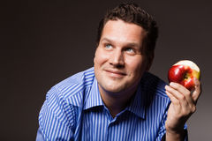 Diet nutrition. Happy man eating apple fruit. Diet and nutrition. Happy young man eating apple seasonal fruit on dark gray. Guy recommending healthy nutrition stock image