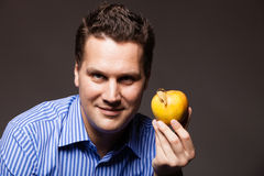 Diet nutrition. Happy man holding apple fruit. Diet and nutrition. Happy young man holding apple seasonal fruit on dark gray. Guy recommending healthy nutrition royalty free stock photo