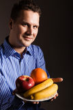 Diet nutrition. Happy young man holding fruits. Stock Photos
