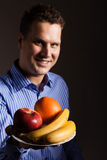 Diet nutrition. Happy young man holding fruits. Royalty Free Stock Image