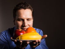 Diet nutrition. Happy young man smelling fruits. Stock Photos