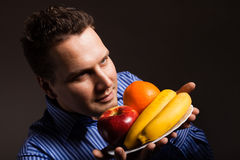 Diet nutrition. Happy young man smelling fruits. Stock Images
