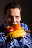 Diet nutrition. Happy young man smelling fruits. Stock Image