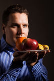Diet nutrition. Happy young man smelling fruits. Stock Photography