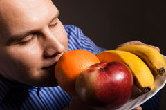 Diet nutrition. Happy young man smelling fruits. Royalty Free Stock Image
