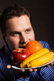 Diet nutrition. Happy young man smelling fruits. Royalty Free Stock Photo