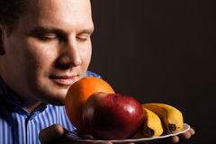 Diet nutrition. Happy young man smelling fruits. Royalty Free Stock Images