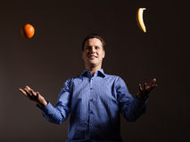 Diet nutrition. Man juggling with tropical fruits Royalty Free Stock Photography
