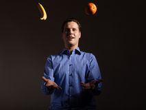 Diet nutrition. Man juggling with tropical fruits Stock Photography