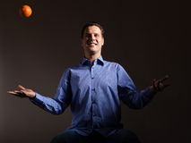 Diet nutrition. Man throwing orange tropical fruit Royalty Free Stock Photo