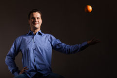 Diet nutrition. Man throwing orange tropical fruit Royalty Free Stock Photos