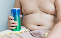 Diet. Obese fat boy holding soft drink can. Diet. Obese fat boy holding soft drink can on gray background royalty free stock photo