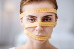 Face of a serious young woman. Diet obsession. Face of a serious young woman wrapped in the centimeter tape Royalty Free Stock Images
